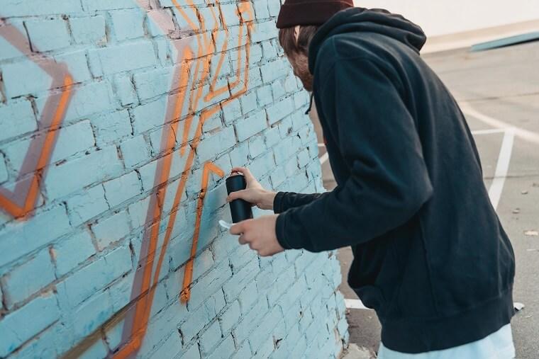 Graffiti aanbrengen op blauwe muur
