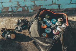 Rugtas met spuitbussen, handschoenen en gasmasker